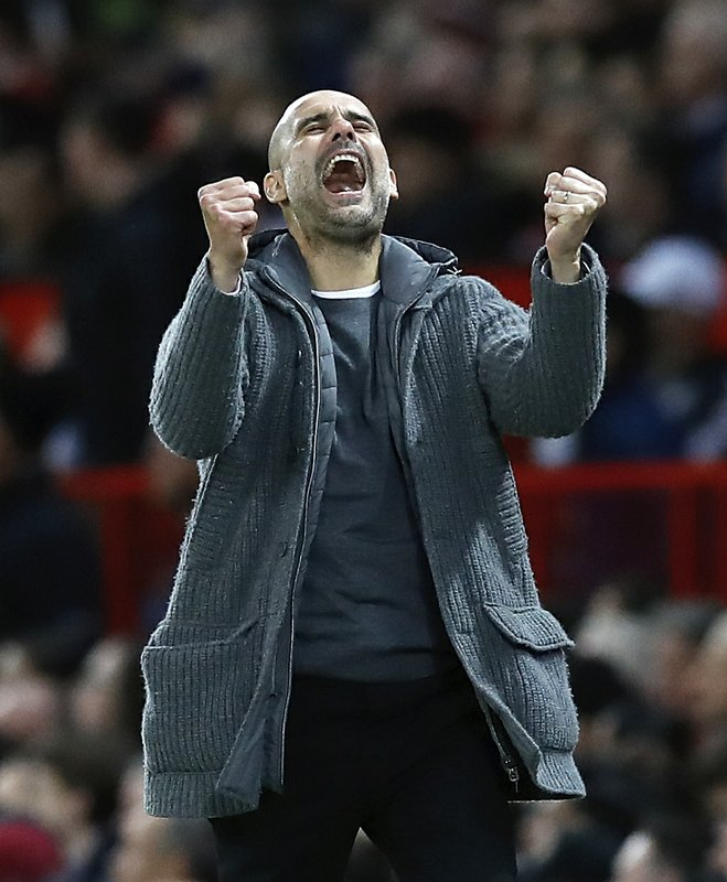 Manchester City manager Pep Guardiola celebrates his side's second goal during the English Premier League soccer match between Manchester United and Manchester City at Old Trafford Stadium in Manchester, England, Wednesday April 24, 2019.(Martin Rickett, PA via AP)