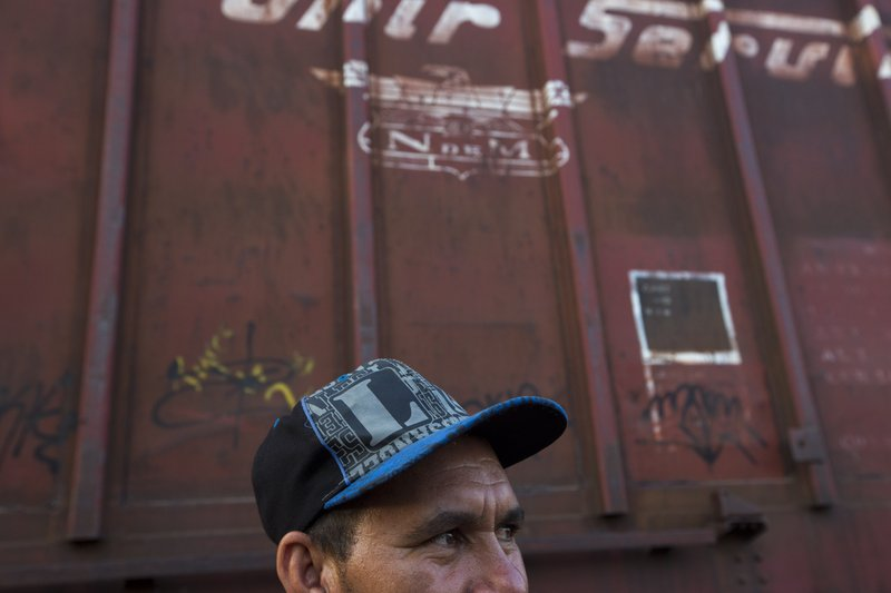 Honduran migrant Jose Vallecillo waits during a rest stop on his trip into Mexico, at a railroad track, before the freight train he hopes to ride along with his family leaves, in Arriaga, Chiapas state, Mexico, Wednesday, April 24, 2019. (AP Photo/Moises Castillo)