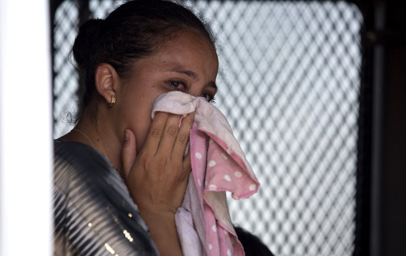 A Guatemalan migrant cries after being taken into custody by Mexican immigration agents, as she sits in an immigration vehicle after her journey to the US-Mexico border came to a stop, near Santo Domingo Zanatepec, Oaxaca state, Mexico, Wednesday, April 24, 2019. (AP Photo/Moises Castillo)