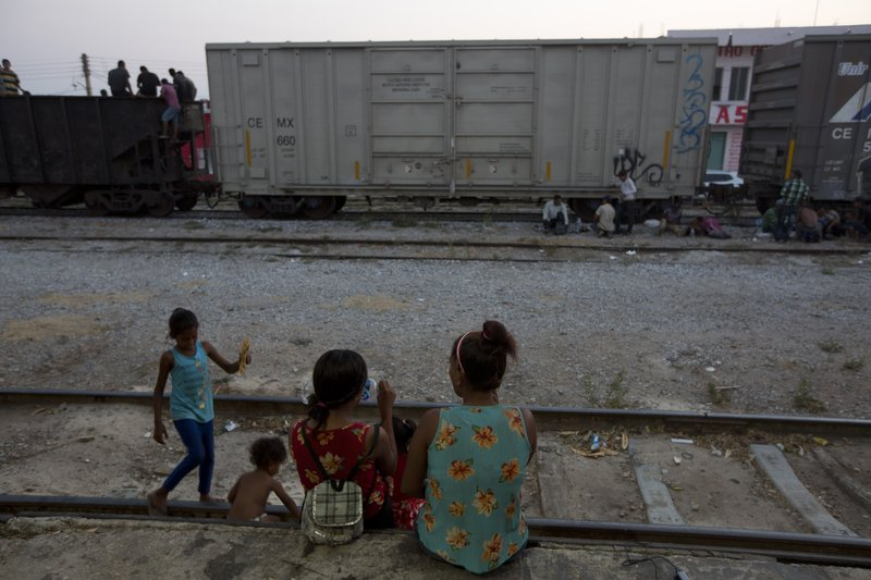 A Central American migrant woman with children rest on the railroad track during their journey toward the US-Mexico border in Arriaga, Chiapas state, Mexico, Wednesday, April 24, 2019. (AP Photo/Moises Castillo)