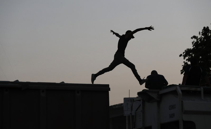 A Central American migrant jumps from one freight train car to another, before the train leaves Arriaga, Chiapas state, Mexico, Wednesday, April 24, 2019. (AP Photo/Moises Castillo)