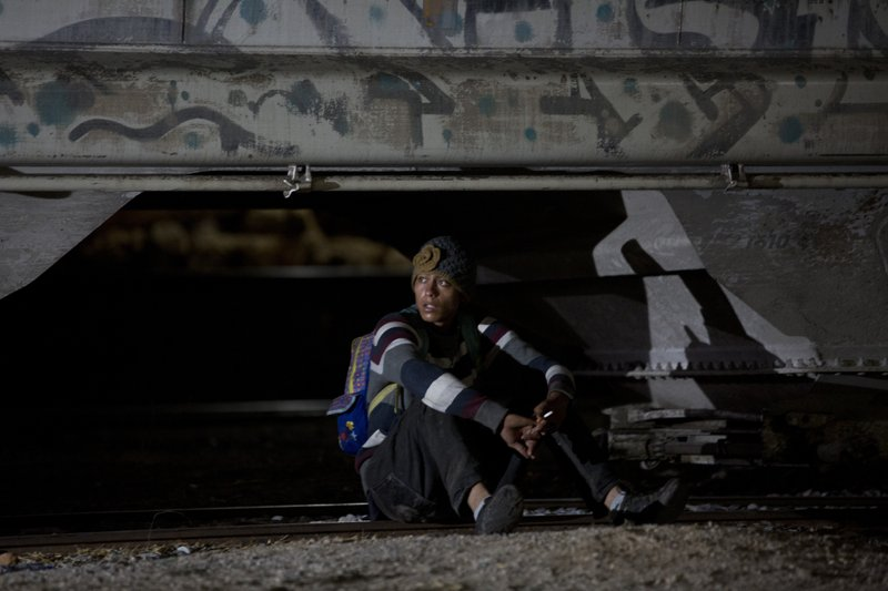 A Central American migrant sits on the railway tracks after Mexican immigration agents drove near the train station in Arriaga, Chiapas State, Mexico, early Thursday, April 25, 2019. (AP Photo/Moises Castillo)