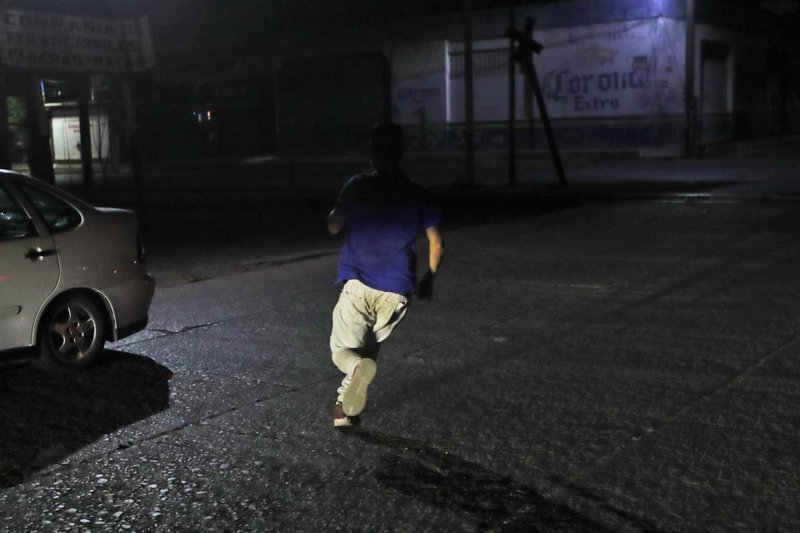 A Central American migrant runs as Mexican immigration agents drive near the train station in Arriaga, Chiapas State, Mexico, early Thursday, April 25, 2019. (AP Photo/Moises Castillo)