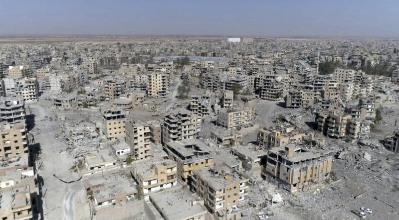 FILE - This Oct. 19, 2017 file photo, a frame grab made from drone video shows damaged buildings in Raqqa, Syria. (AP Photo/Gabriel Chaim, File)