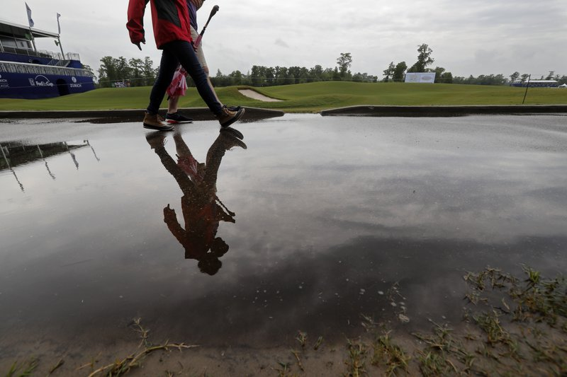 People walk on the largely empty course during a weather delay for the first round of the PGA Zurich Classic golf tournament at TPC Louisiana in Avondale, La. (AP Photo/Gerald Herbert)