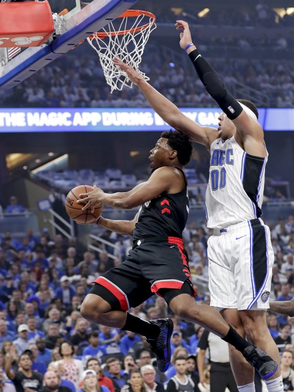 Toronto Raptors' Kyle Lowry, left, goes in to shoot against Orlando Magic's Aaron Gordon (00) during the first half in Game 3 of a first-round NBA basketball playoff series, Friday, April 19, 2019, in Orlando, Fla. (AP Photo/John Raoux)