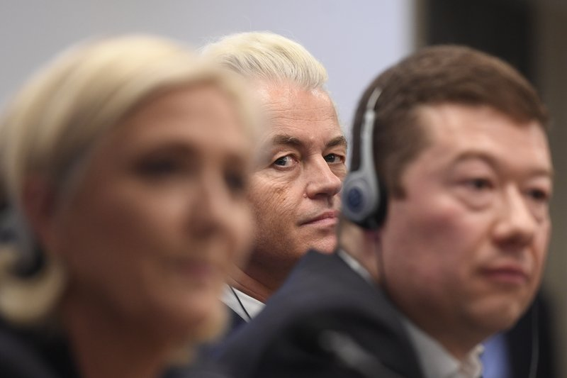 Leader of Dutch Party for Freedom Geert Wilders, center, peers at the photographer, as leader of French National Front Marine Le Pen, left, and Czech far-right Freedom and Direct Democracy (SPD) head Tomio Okamura, right, sit by as they attend a press conference before the rally against