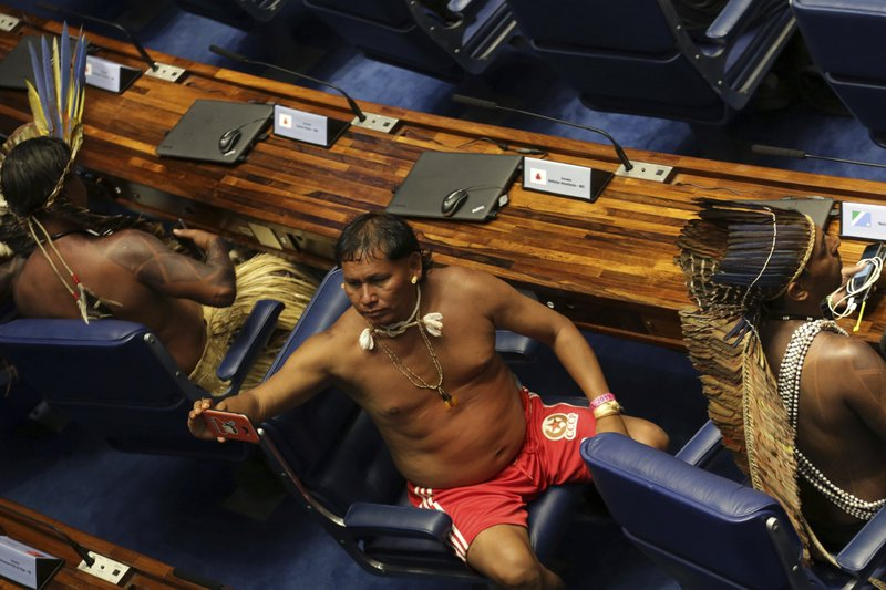 A Guarani man poses for a selfie while sitting in the lower house chamber in Brasilia, Brazil, Thursday, April 25, 2019. (AP Photo/Eraldo Peres)