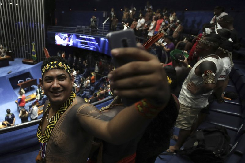 An indigenous man poses for a selfie during a meeting with lawmakers to discuss land rights and the Chamber of Deputies' role in the protection of the environment in Brasilia, Brazil, Thursday, April 25, 2019. (AP Photo/Eraldo Peres)