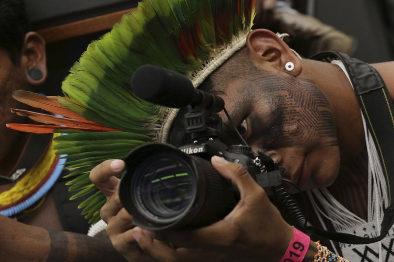 An indigenous man films a meeting with lawmakers to discuss land rights and the Chamber of Deputies' role in the protection of the environment in Brasilia, Brazil, Thursday, April 25, 2019. (AP Photo/Eraldo Peres)