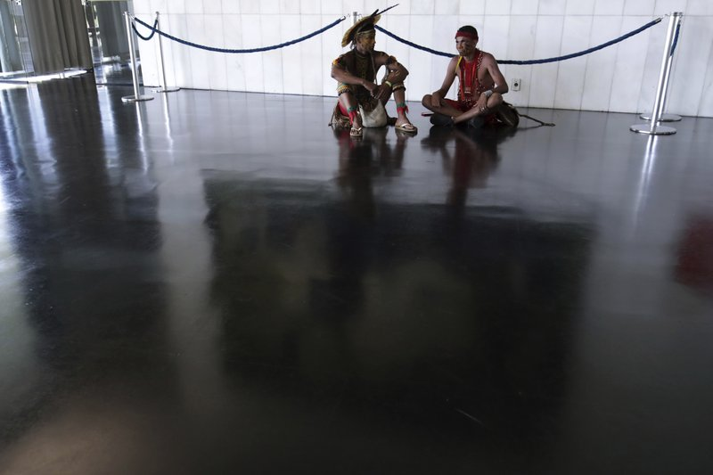 Indigenous men wait to attend a meeting with lawmakers to discuss land rights and the Chamber of Deputies' role in the protection of the environment in Brasilia, Brazil, Thursday, April 25, 2019. (AP Photo/Eraldo Peres)