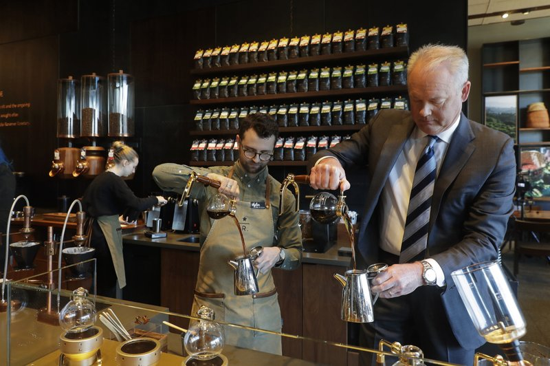 FILE- In this March 5, 2019, file photo Kevin Johnson, right, CEO of Starbucks, makes coffee using a siphon method alongside barista Dylan George, left, as Johnson visits the company's Starbucks Reserve store in the company's headquarters building in Seattle's SODO neighborhood. (AP Photo/Ted S. Warren, File)