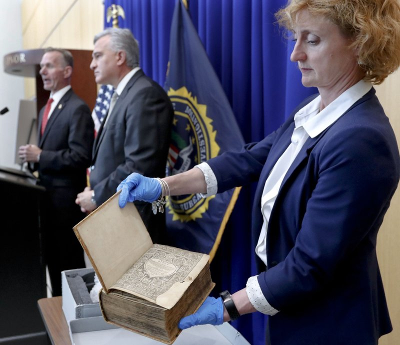FBI Special Agent in Charge Robert Jones, left, and Allegheny County District Attorney Stephen Zappala, center, talk about the efforts and ultimate recovery of the Breeches Edition Bible that FBI supervisory special agent Shawn Brokos, right, holds during a news conference, Thursday, April 25, 2019, in Pittsburgh. (AP Photo/Keith Srakocic)