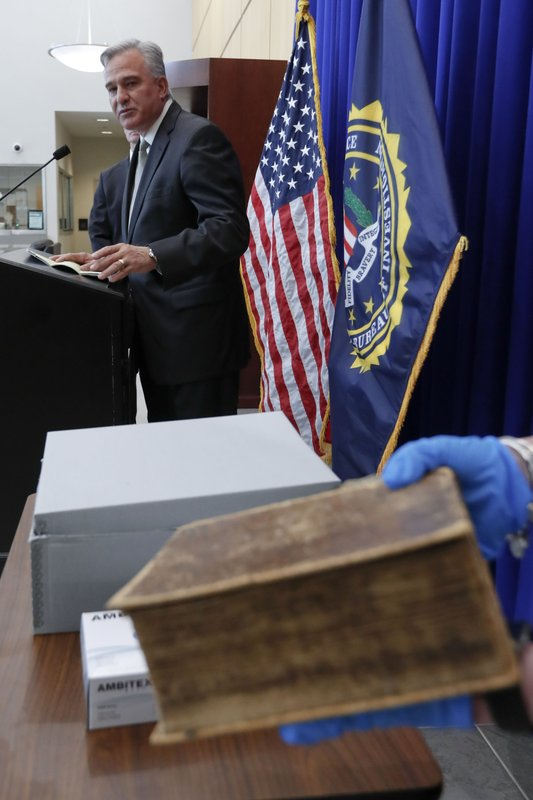 Allegheny County District Attorney Stephen Zappala talks about the efforts and ultimate recovery of the Breeches Edition Bible that FBI supervisory special agent Shawn Brokos holds during a news conference, Thursday, April 25, 2019, in Pittsburgh. (AP Photo/Keith Srakocic)