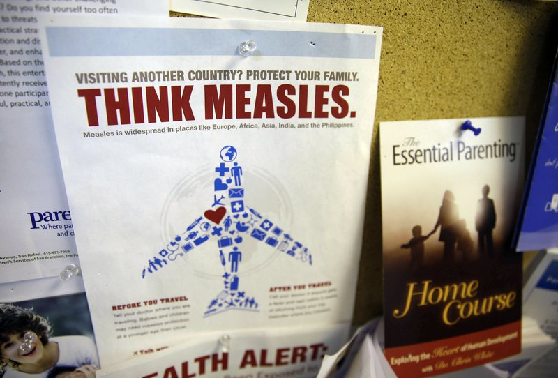 FILE - In this Feb. 6, 2015, file photo, a flyer educating parents about measles is displayed on a bulletin board at a pediatrics clinic in Greenbrae, Calif. (AP Photo/Eric Risberg, File)