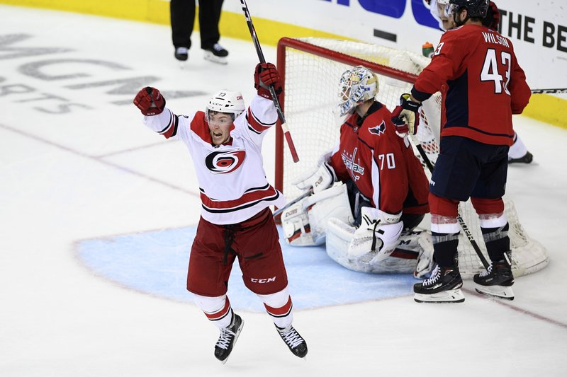 Carolina Hurricanes left wing Brock McGinn, left, celebrates his game-winning goal during double overtime of Game 7 of an NHL hockey first-round playoff series against Washington Capitals goaltender Braden Holtby (70) and right wing Tom Wilson (43), Wednesday, April 24, 2019, in Washington. (AP Photo/Nick Wass)