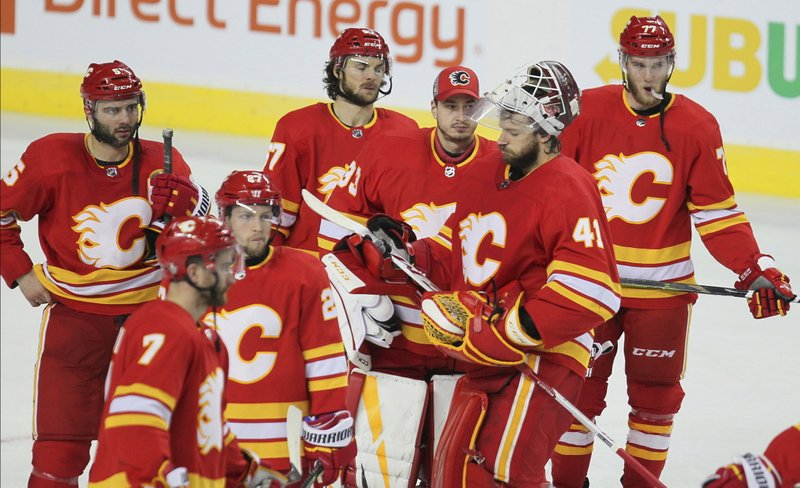 Calgary Flames players stand on the ice after losing 5-1 to the Colorado Avalanche during Game 5 of an NHL hockey first-round playoff series Friday, April 19, 2019, in Calgary, Alberta. (Dave Chidley/The Canadian Press via AP)