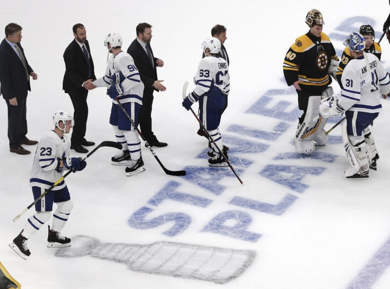 Boston Bruins goaltender Tuukka Rask and Toronto Maple Leafs goaltender Frederik Andersen, top right, talk before shaking hands after the third period of Game 7 of an NHL hockey first-round playoff series, Tuesday, April 23, 2019, in Boston. (AP Photo/Charles Krupa)