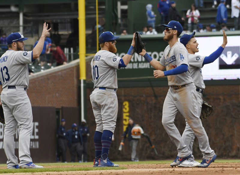 The Los Angeles Dodgers celebrate their 2-1 win against the Chicago Cubs in a baseball game, Thursday, April, 25, 2019, in Chicago. (AP Photo/David Banks)