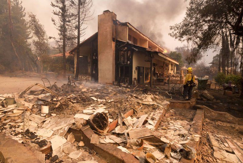 File - In this Nov. 9, 2018, file photo, a firefighter keeps watch as the charred remains of a burned out home are seen during the Woolsey Fire in Malibu, Calif. (AP Photo/Ringo H.W. Chiu, File)