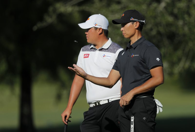 Sungjae Im, left, and Whee Kim, both of South Korea wait for their turn to putt on the first green, during the first round of the PGA Zurich Classic golf tournament at TPC Louisiana in Avondale, La. (AP Photo/Gerald Herbert)