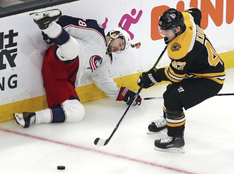 Columbus Blue Jackets right wing Oliver Bjorkstrand, left, slams into the boards after being upended by Boston Bruins defenseman Torey Krug, right, while chasing the puck during the first period of Game 1 of an NHL hockey second-round playoff series, Thursday, April 25, 2019, in Boston. (AP Photo/Charles Krupa)