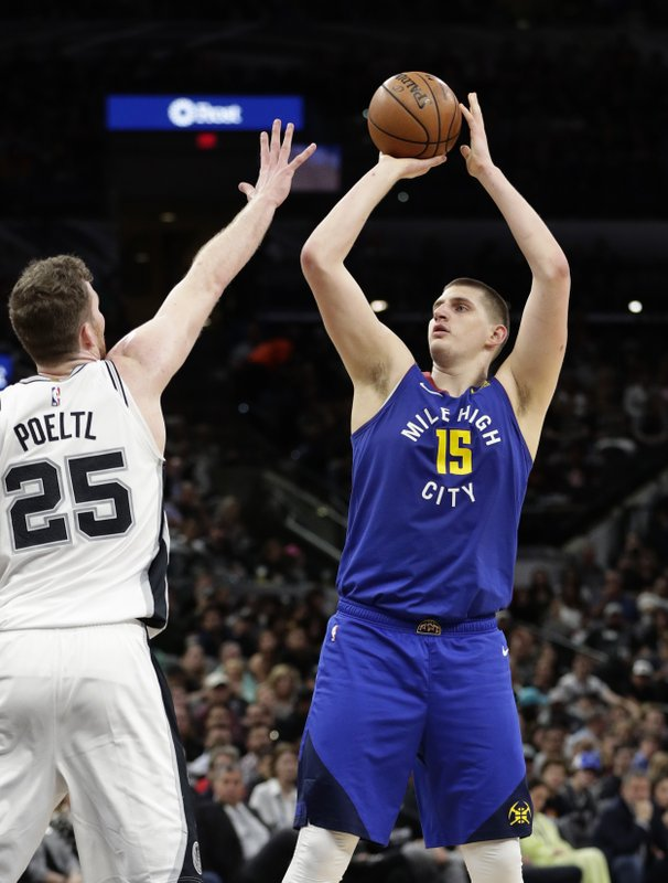 Denver Nuggets center Nikola Jokic (15) shoots over San Antonio Spurs center Jakob Poeltl (25) during the first half of Game 6 of an NBA basketball playoff series, Thursday, April 25, 2019, in San Antonio. (AP Photo/Eric Gay)