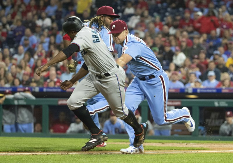 Philadelphia Phillies first baseman Rhys Hoskins, right, tags out Miami Marlins' Curtis Granderson, left, as he gets caught in a run down during the third inning of a baseball game, Thursday, April 25, 2019, in Philadelphia. (AP Photo/Chris Szagola)