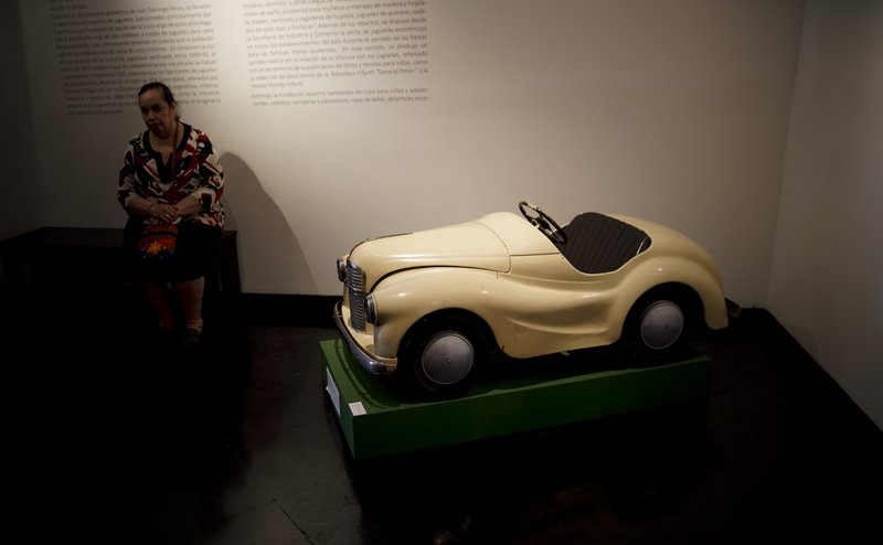 A visitor sits near a toy pedal car of the