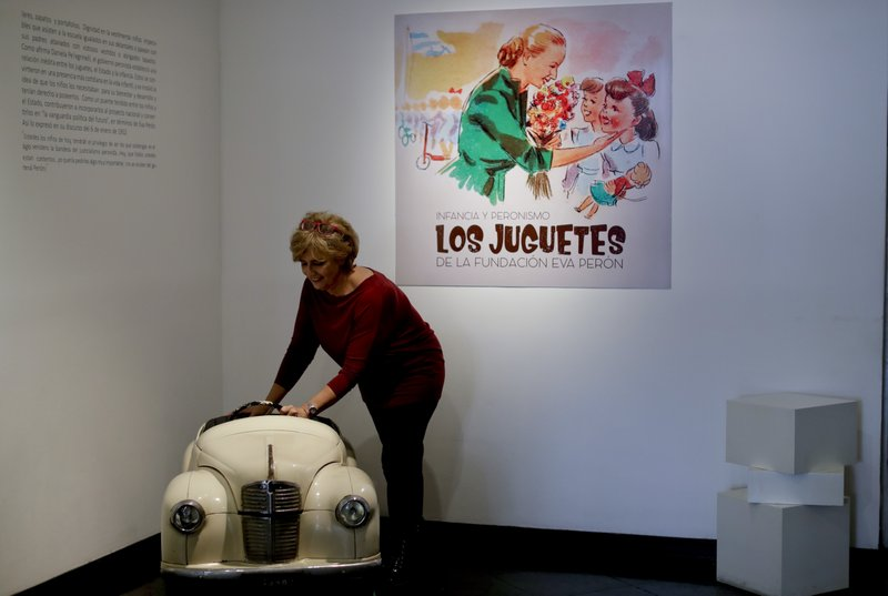 Marcela Genés, curator of the Evita museum, poses for a photo with a toy pedal car at the