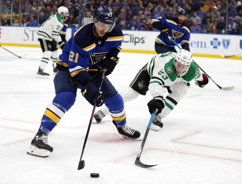 St. Louis Blues center Tyler Bozak (21) is challenged by Dallas Stars' Esa Lindell (23) for control of the puck during the second period in Game 1 of an NHL second-round hockey playoff series Thursday, April 25, 2019, in St. (AP Photo/Jeff Roberson)