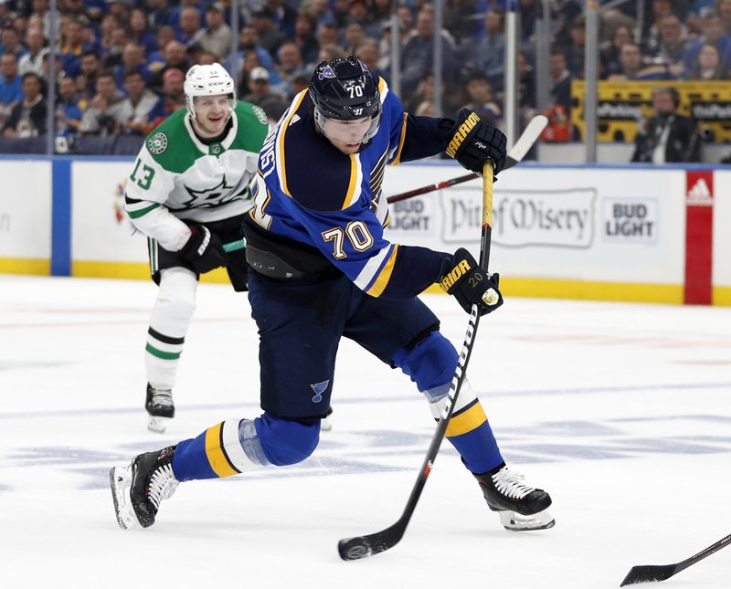 St. Louis Blues center Oskar Sundqvist (70) takes a shot as Dallas Stars' Mattias Janmark (13) looks on during the second period in Game 1 of an NHL second-round hockey playoff series Thursday, April 25, 2019, in St. (AP Photo/Jeff Roberson)