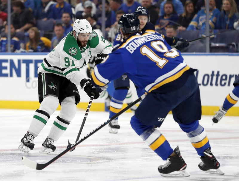 Dallas Stars center Tyler Seguin (91) makes a pass as St. Louis Blues' Jay Bouwmeester (19) defends during the first period in Game 1 of an NHL second-round hockey playoff series, Thursday, April 25, 2019, in St. (AP Photo/Jeff Roberson)