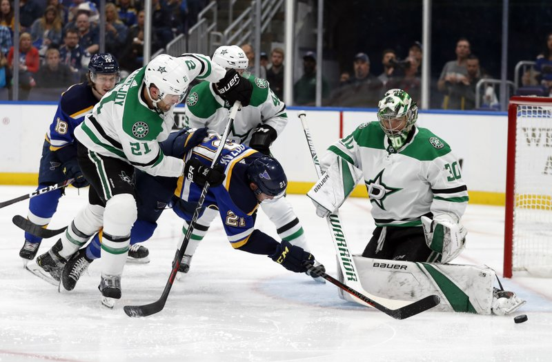 St. Louis Blues center Tyler Bozak (21) has his shot blocked by Dallas Stars' Ben Bishop (30) who receives help from defenseman Ben Lovejoy (21) defending the net during the second period in Game 1 of an NHL second-round hockey playoff series Thursday, April 25, 2019, in St. (AP Photo/Jeff Roberson)