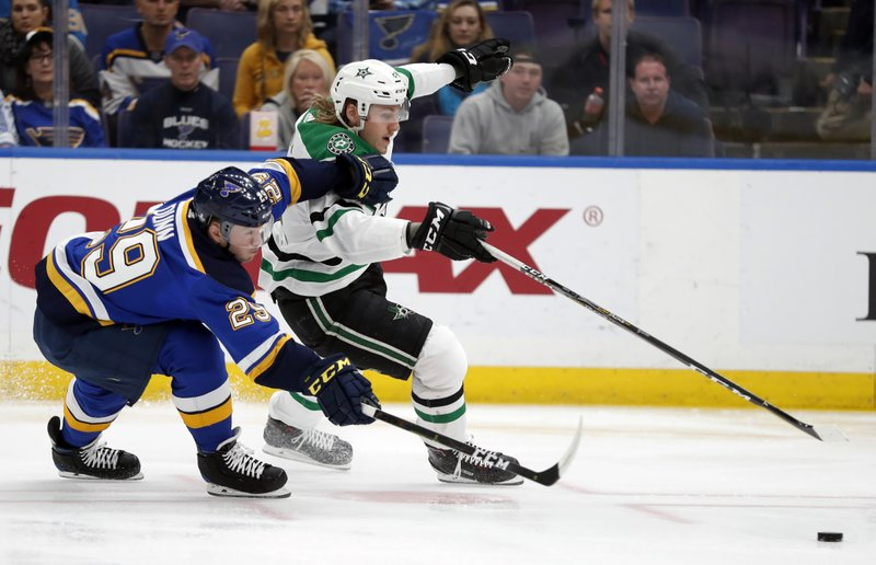 St. Louis Blues defenseman Vince Dunn (29) and Dallas Stars left wing Roope Hintz (24) chase after a loose puck during the first period in Game 1 of an NHL second-round hockey playoff series Thursday, April 25, 2019, in St. (AP Photo/Jeff Roberson)