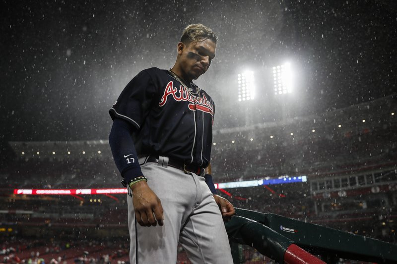 Atlanta Braves' Johan Camargo walks into the dugout during a rain delay in the seventh inning of a baseball game against the Cincinnati Reds, Thursday, April 25, 2019, in Cincinnati. (AP Photo/John Minchillo)