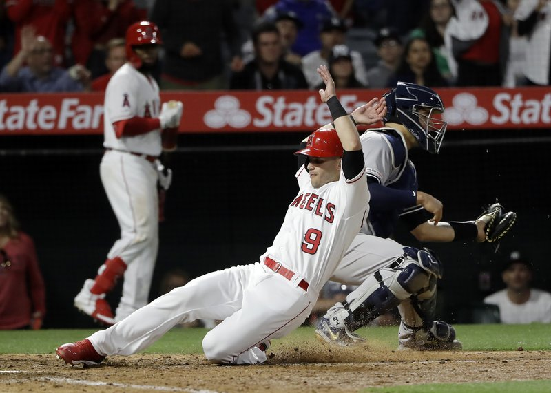 Los Angeles Angels' Tommy La Stella (9) scores past New York Yankees catcher Gary Sanchez on a single from David Fletcher during the sixth inning of a baseball game Thursday, April 25, 2019, in Anaheim, Calif. (AP Photo/Marcio Jose Sanchez)
