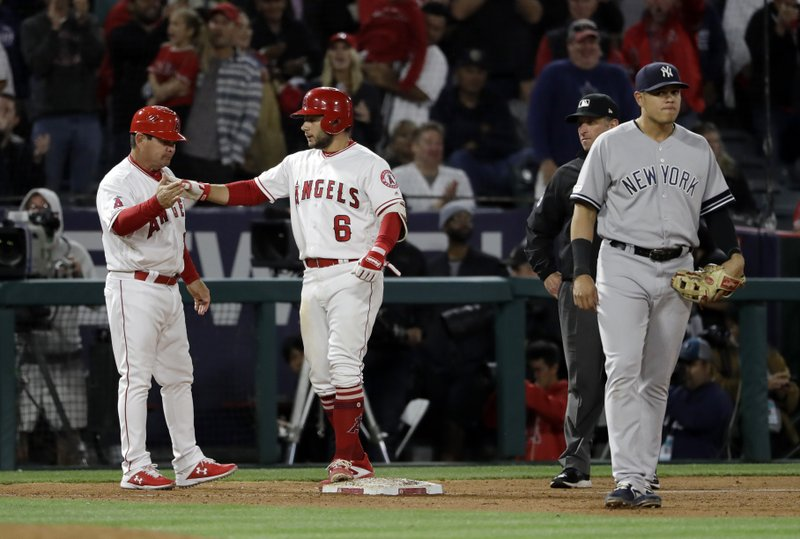 Los Angeles Angels' David Fletcher (6) celebrates at third base with coach Mike Gallego, right, after Fletcher drove in three runs with a bases loaded triple during the seventh inning of a baseball game against the New York Yankees Thursday, April 25, 2019, in Anaheim, Calif. (AP Photo/Marcio Jose Sanchez)