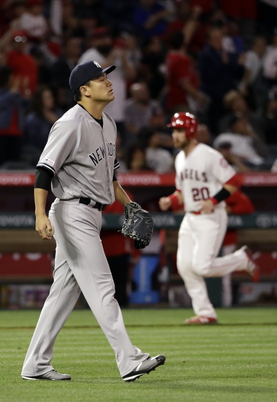 New York Yankees starting pitcher Masahiro Tanaka, left, walks back to the mound after giving up a two-run home run to Los Angeles Angels' Tommy La Stella during the fifth inning of a baseball game Thursday, April 25, 2019, in Anaheim, Calif. (AP Photo/Marcio Jose Sanchez)