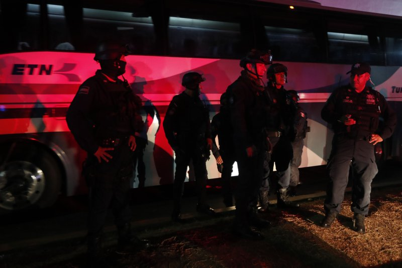 Federal police stand guard by a bus that will transfer migrants to another location, at an immigration detention center in Tapachula, Chiapas state, Mexico, Thursday, April 25, 2019. (AP Photo/Moises Castillo)