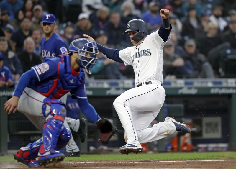 Seattle Mariners' Ryon Healy, right, slides in safely to home to score as Texas Rangers catcher Isiah Kiner-Falefa waits for the ball in the first inning of a baseball game Thursday, April 25, 2019, in Seattle. (AP Photo/Elaine Thompson)