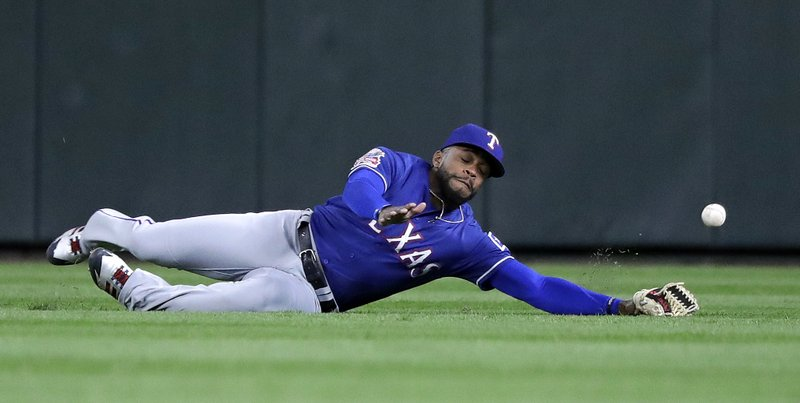 Texas Rangers center fielder Delino DeShields dives for and misses a fly ball from Seattle Mariners' Dylan Moore for a double in the fifth inning of a baseball game Thursday, April 25, 2019, in Seattle. (AP Photo/Elaine Thompson)