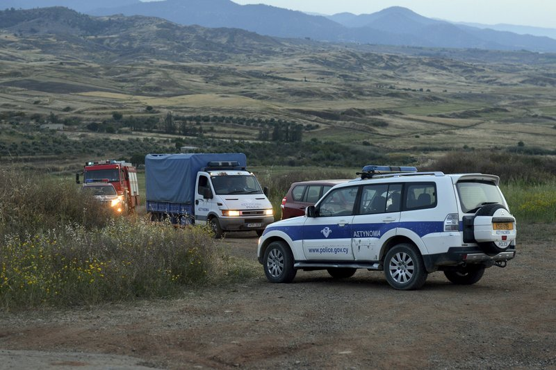 A police truck, rear left, carries a body found after Cypriot investigators and police officers searched at a field outside of Orounta village, near the capital Nicosia, Cyprus, Thursday, April 25, 2019. (AP Photo)