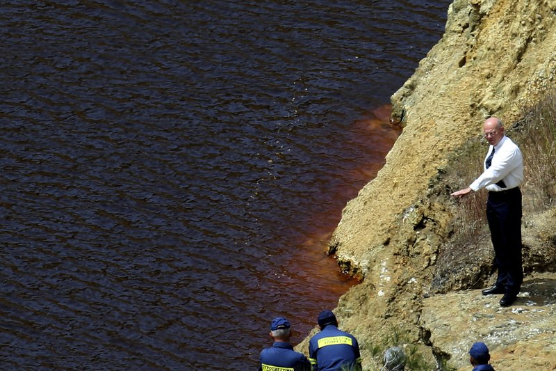 Firefighters and investigators search the man made lake near the village of Mitsero outside of the capital Nicosia, Cyprus, Friday, April 26, 2019. (AP Photo/Petros Karadjias)