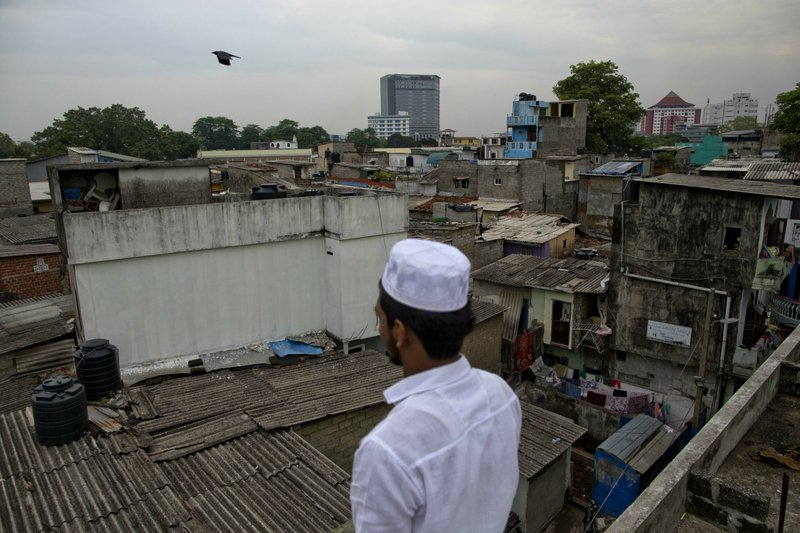 A Muslim volunteer stands in a roof of a mosque to spot possible attackers during Friday prayers in Colombo, Sri Lanka, Friday, April 26, 2019. (AP Photo/Gemunu Amarasinghe)