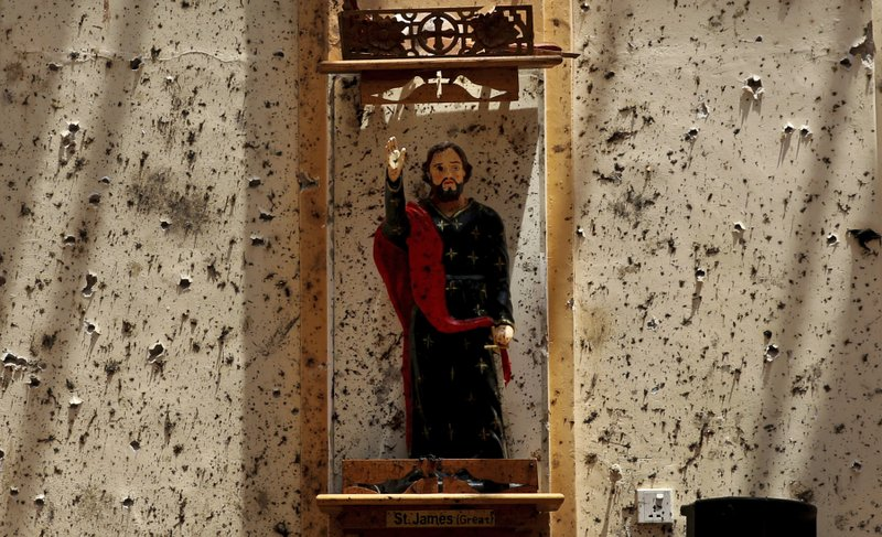 In this Thursday, April 25, 2019 photo, a statue of St. James stands on a wall speckled with fragments of shrapnel at St. (AP Photo/Manish Swarup)