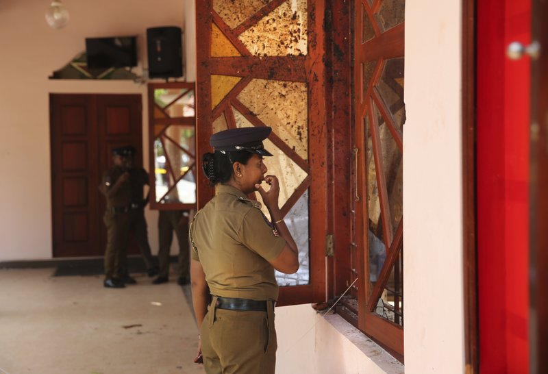 In this Thursday, April 25, 2019 photo, a Sri Lankan policewoman looks at the damage inside St. Sebastian's Church, one of the sites of Easter Sunday's bombings, in Negombo, north of Colombo, Sri Lanka. (AP Photo/Manish Swarup)