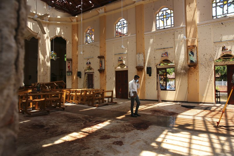 In this Thursday, April 25, 2019 photo, a surveyor walks inside the damaged St. Sebastian's Church where a suicide bomber blew himself up on Sunday Easter in Negombo, north of Colombo, Sri Lanka. (AP Photo/Manish Swarup)