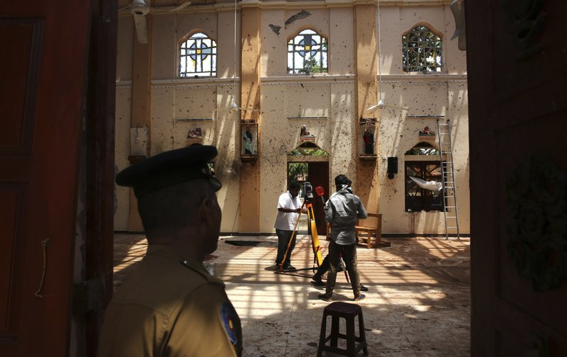 In this Thursday, April 25, 2019 photo, a policeman stands guard, as surveyors work at St. Sebastian's Church, where a suicide bomber blew himself up on Easter Sunday in Negombo, north of Colombo, Sri Lanka. (AP Photo/Manish Swarup)