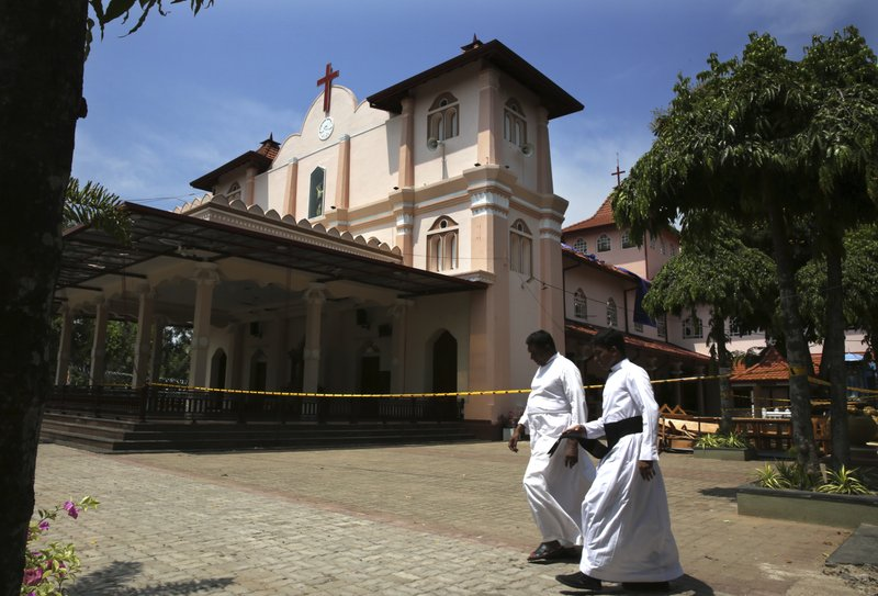 In this Thursday, April 25, 2019 photo, Catholic priests walk outside St. Sebastian's Church, where a suicide bomber blew himself up on Easter Sunday in Negombo, north of Colombo, Sri Lanka. (AP Photo/Manish Swarup)